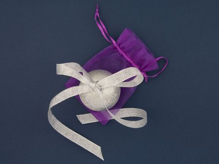 Christmas decoration silver ball with silver bow and lilac bag on blue background photo