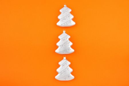 Three Christmas decoration silver firs on orange background. Modern Christmas card photo