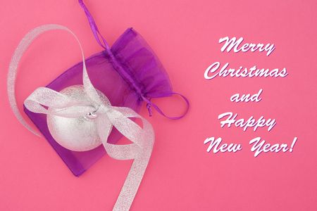 Christmas decoration silver ball with silver bow and lilac bag on pink background photo
