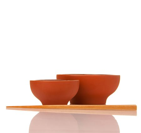 Emty asian ceramics bowls and wood chopsticks on white with reflection photo