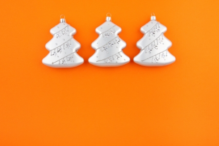 Three Christmas decoration silver firs on orange paper background