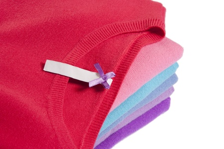 Pile of multicolored knitted clothes with blank label macro on white photo