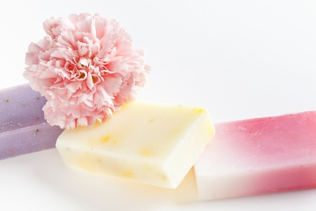 Three soap bars with natural ingredients and flower photo