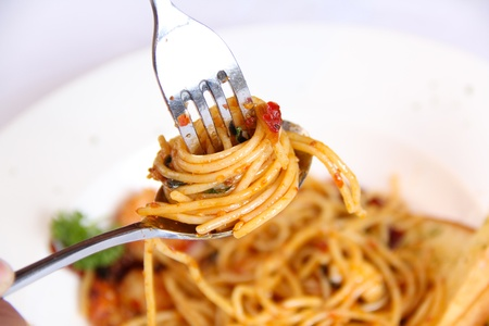 Spaghetti hanging on a fork on whitebackground photo