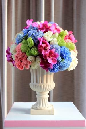 florero: Arregle las flores en un jarr�n romano blanco