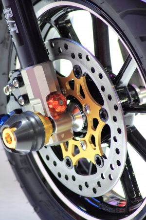 brake caliper: Closeup detail of a racing motorcycles front wheel. This is the brake caliper, rotor, rim, tire, and suspension.