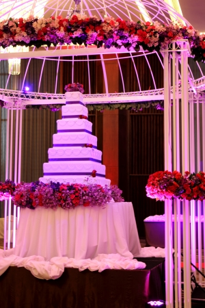 A tier white and purple square wedding cake and dome photo