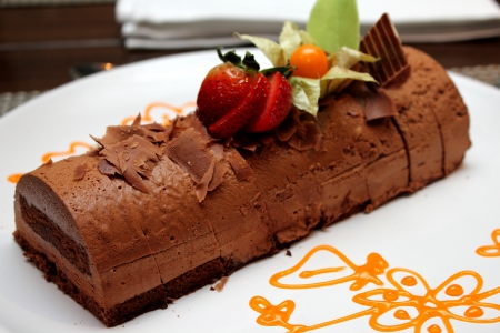 Plate of dark chocolate mousse cake on white plate photo