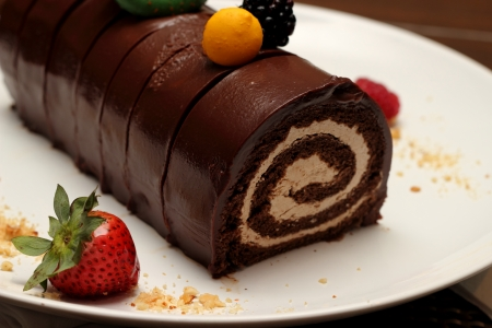 A piece of mini chocolate log cake with strawberry photo