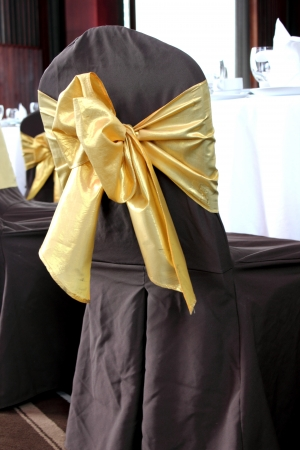 wedding chairs: brown wedding chairs decorated with golden bows Stock Photo