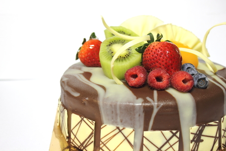 A Chocolate cake and topped with fresh fruit.  photo
