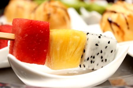 fruit skewers: Plato de brochetas de frutas con un plato de comida de las fiestas saludable.