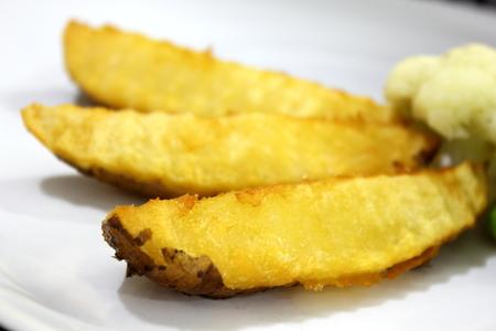 Fresh homemade crispy fried potato wedges on plate  photo
