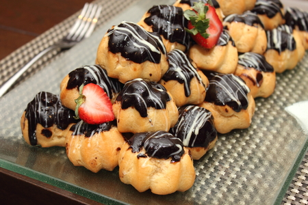profiterole: Eclair with hot chocolate fudge on food table