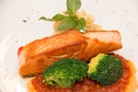 stake: Stake from a salmon with vegetables on a plate. Closeup. Stock Photo
