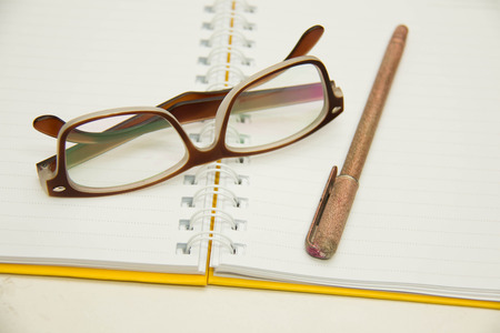 ruled paper: Ballpoint ink writing pen ready for taking notes on a spiral bound study and composition notebook open to a blank ruled paper sheet with reading glasses over white.