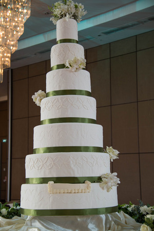 tiered: A tall  flowers next to a wedding cake. Stock Photo