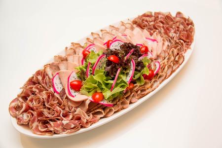 Un plato de embutidos mixtos sobre blanco Foto de archivo