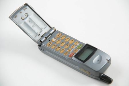 communicates: Solid color background and shabby gray old mobile phones.