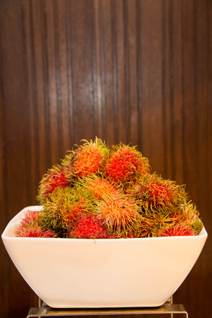 A Rambutan in bowle on a wood background.
