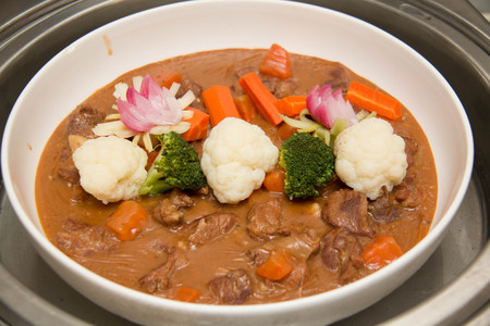 crock pot: Beef stew in a white crock pot, ready to serve.