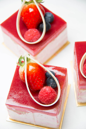 A peice of strawberry cake as closeup on a white plate
