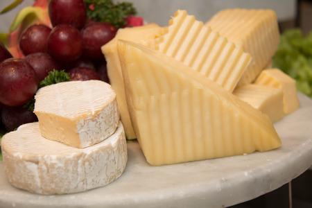 tabla de quesos: Placa de queso con camembert, montaña y queso suizo en una tarjeta Ston Foto de archivo