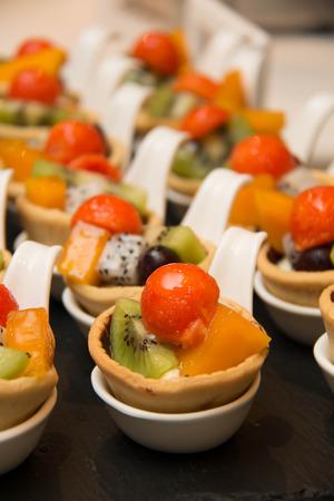 custard slices: Mixed fruit tart. A custard base tart filling with various fruits on top. Stock Photo