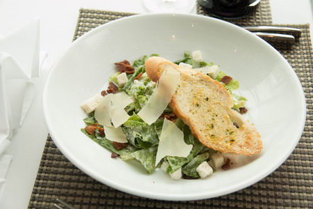 sinners: Bowl of caesar salad with lettuce and garlic bread