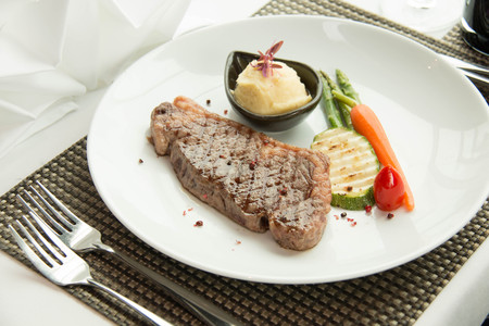 beefsteaks: beef steak with sear marks with , asparagus, and red carrot garnish.