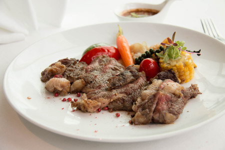 Freshly cooked rare sirloin steak  on a white plate