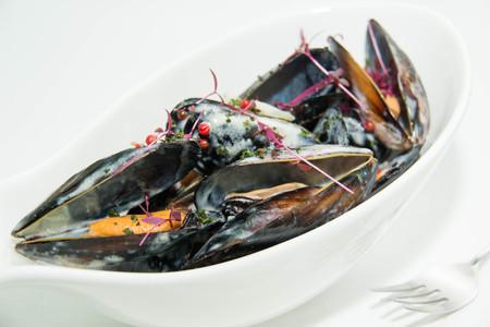 almeja: Plato de mejillones con salsa de crema en el paño blanco de mesa