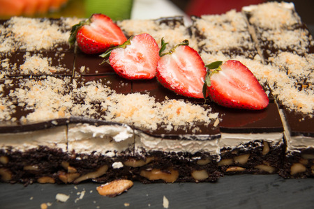Slices of Chocolate Nut Brownies on top fresh strawberry Stock Photo