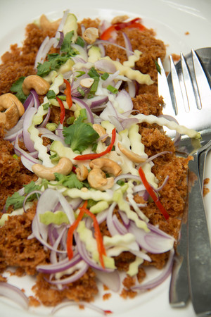 Crispy catfish salad in a white plate
