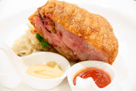 German fried pork leg and sauce on white plate