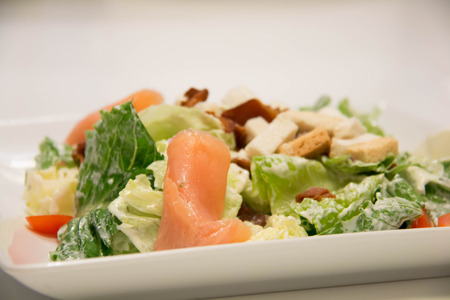 A Caesar salad with salmon and parmesan cheese