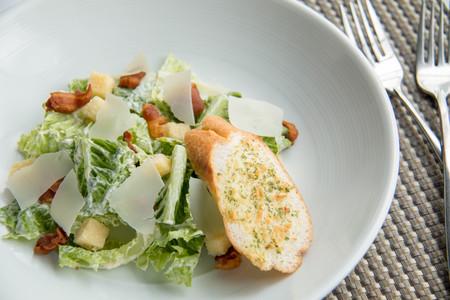 A plated caesar salad with garlic bread