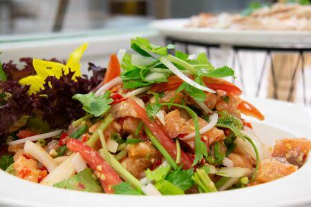Une salade thaïlandaise de saumon épicé sur une assiette blanche