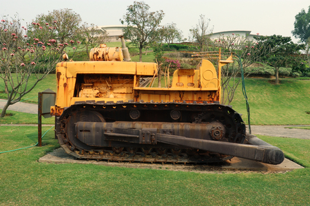 Old yellow rusty crawler tractor in the field. Old crawler tractor on green garden High resolution image gallery.