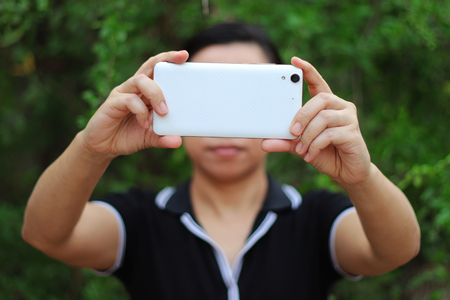 Asian woman holding and using smart phone show back side. High resolution image gallery. Stok Fotoğraf