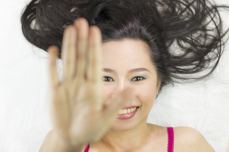 asian women  lying on ground with black long hair. acting smile, happy, and showing stop gesture.