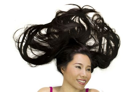 Closeup portrait of happy asian women  lying on ground with black long hair. acting smile, fun,