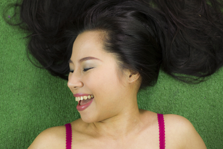 women lying on the green grass, a beautiful and acting funny smile ,Thai woman laying down on green grass. High resolution image gallery.
