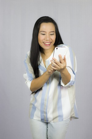 cute beautiful woman in shirt acting playing on phone.  Isolated on gray background. High resolution image gallery. 写真素材
