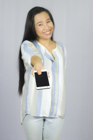 Smiling women holding mobile phone, give a smart phone to you. isolated on gray background. High resolution image gallery. 版權商用圖片