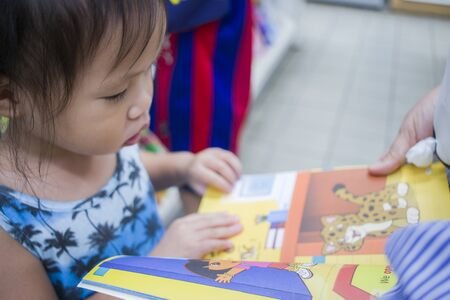 CHIANG MAI,THAILAND-MAY 3,2019 : Little Child explores the bookshelves with mom in book store. High resolution image gallery.