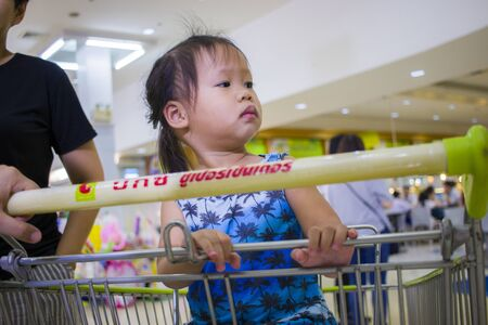 CHIANGMAI,THAILAND-MAY 3,2019 : Asian toddler girl looking for something and sitting in the trolley cart during family shopping in supermarket