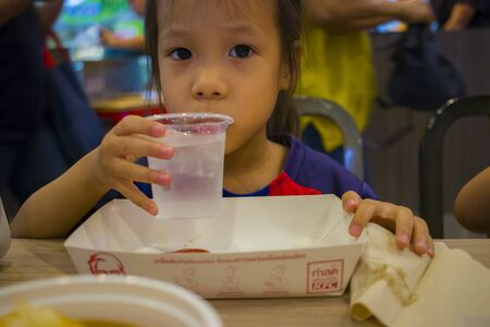 CHIANGMAI,THAILAND-MAY 3,2019 : Little Child eating fried chicken in the background of KFC restaurant.