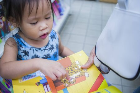 CHIANGMAI,THAILAND-MAY 3,2019 : Little Child explores the bookshelves with mom in book store. High resolution image gallery.