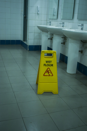 Yellow slippery warning sign, caution wet floor sign in the toilet room High resolution image gallery.